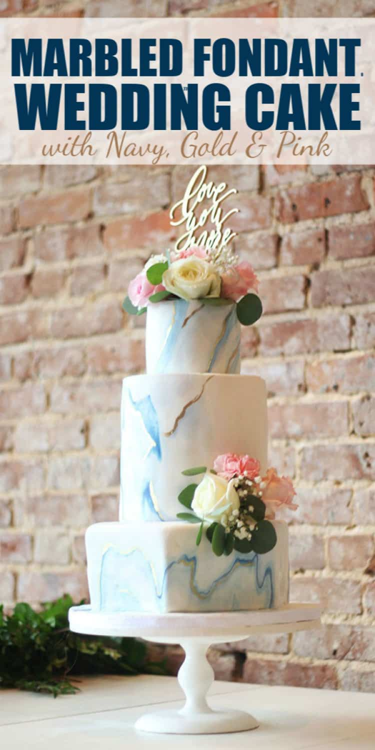 Marbled Fondant Wedding Cake with Navy, Gold and Pink on a white cake stand with brick background and text for Pinterest