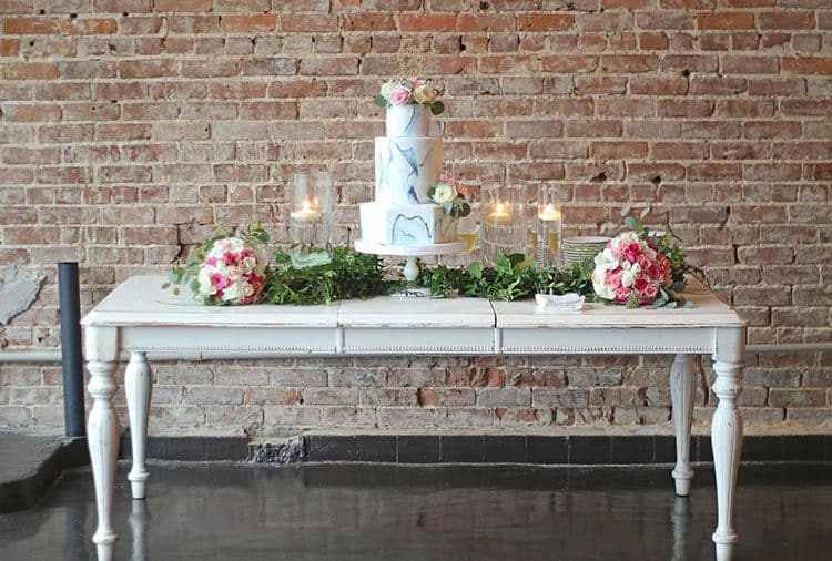Marbled Fondant Wedding Cake with Navy, Gold and Pink on a white table with greenery, pink bouquets, and candles with brick background