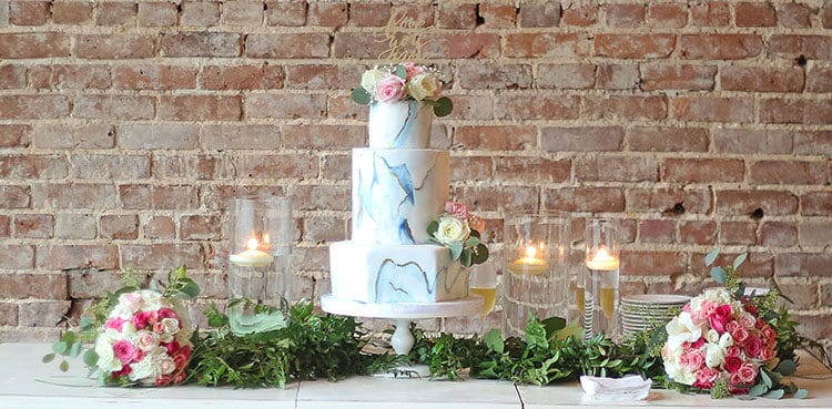 This Marbled Fondant Wedding Cake with Navy, Gold and Pink on table with greenery and pink bouquest and brick background