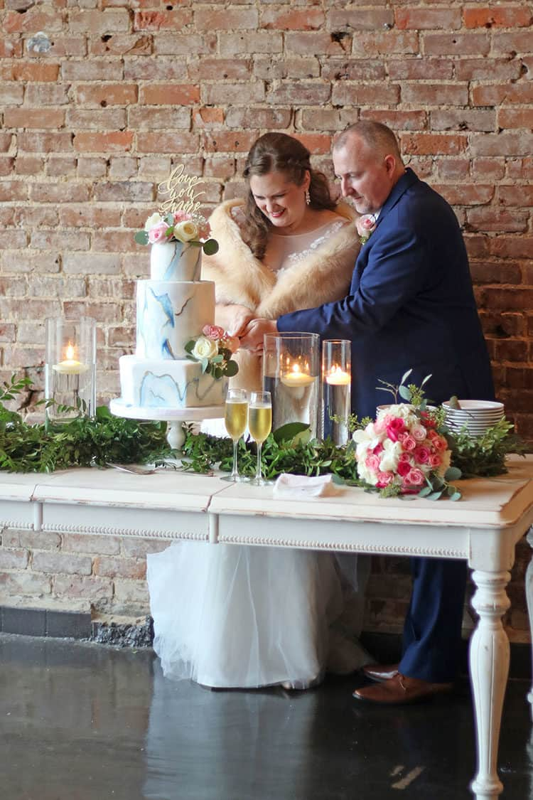 Susan and Stephen cutting the Marbled Fondant Wedding Cake with Navy Gold and Pink