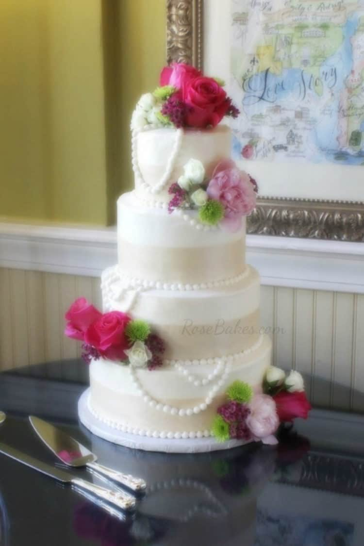 Champagne, Pearls & Hot Pink Flowers Wedding Cake on shiny black table