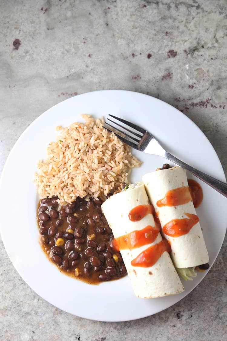 Beef & Beans Soft Tacos with BUSH'S Savory Beans on a white plate with Spanish Rice