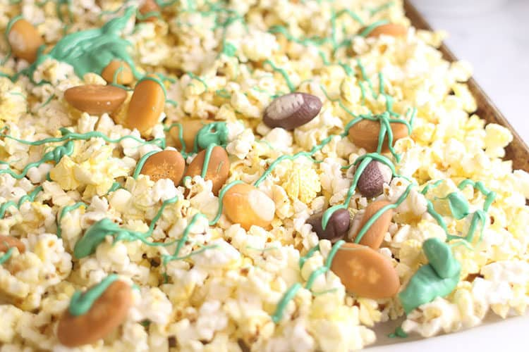 green candy melts drizzled over popcorn for Football Party Snack Mix