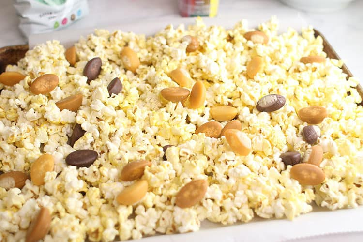 microwave popcorn and football candy corn on cookie sheet for Football Party Popcorn Snack Mix