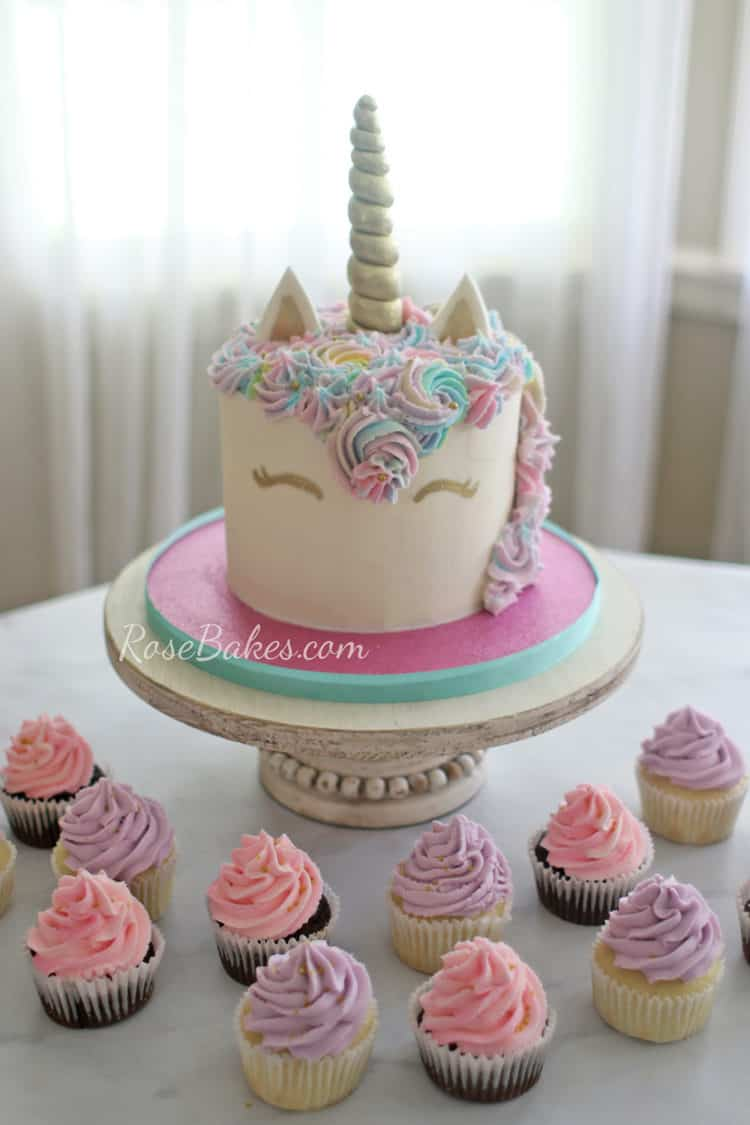 pink blue and purple unicorn cake with pink and purple cupcakes
