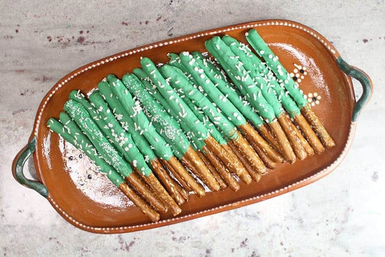 cactus pretzel rods on brown platter with green candy melts and white sprinkles for how to make cactus pretzel rods tutorial