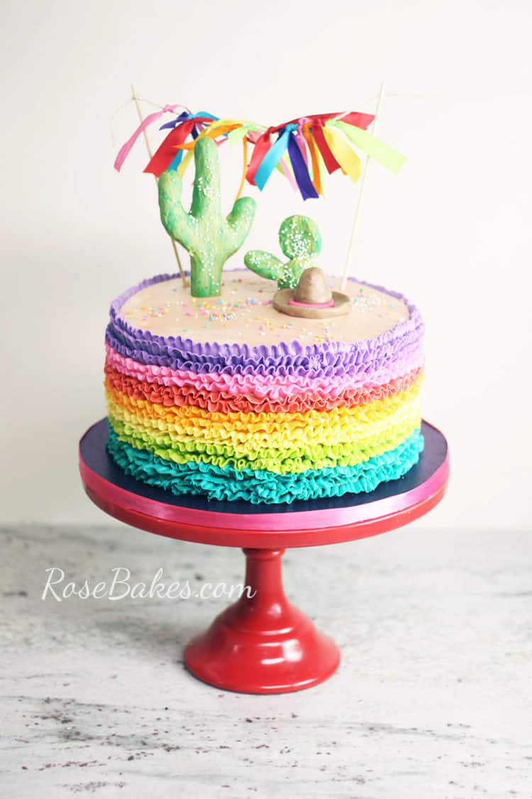 rainbow buttercream ruffles fiesta cake with cactus cake toppers and ribbon bunting on red cake stand