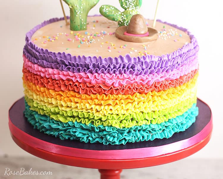 rainbow buttercream ruffles cake on red cake stand with cactus topper for fiesta cake