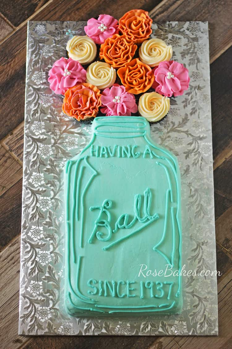 """Having a Ball"" Mason Jar Cake with Flowers on silver cake board"