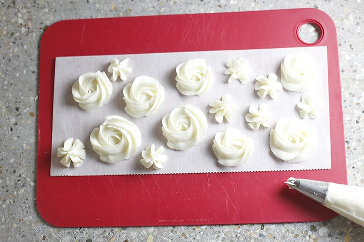 piped buttercream and stars with buttercream on wax paper and cutting board