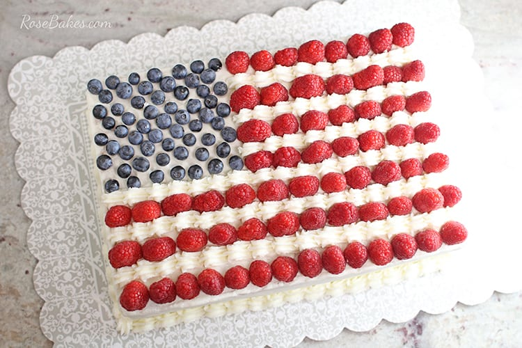 american flag cake with raspberries and blueberries on sheet cake board