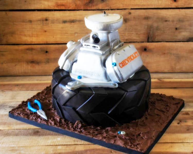 Tire and Engine Cake sitting on cake board made to look like mud