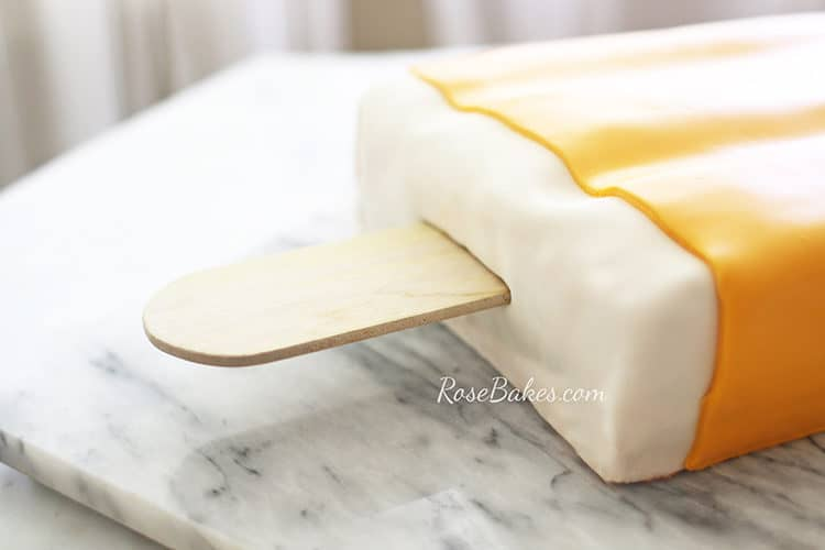 orange creamsicle cake or dreamsicle cake on a marble slab with lauan popsicle stick