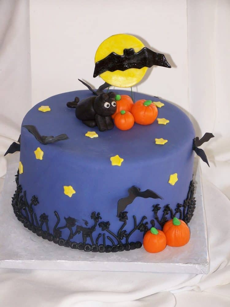 purple cake with black bats, orange pumpkins and a black fondant cat on top perfect for halloween