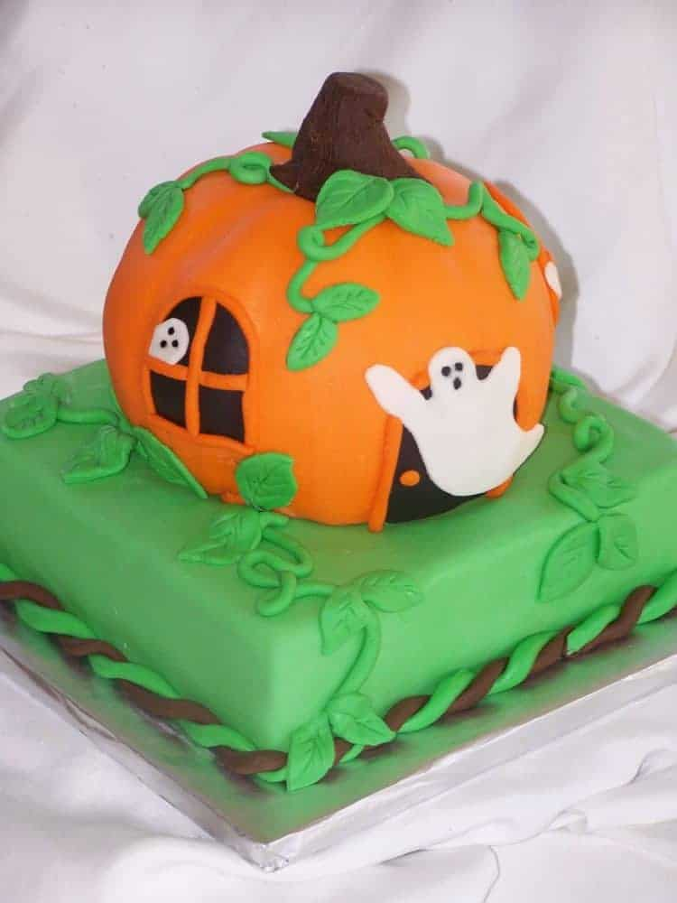 Green square cake with orange pumpkin cake on top with ghosts in the windows