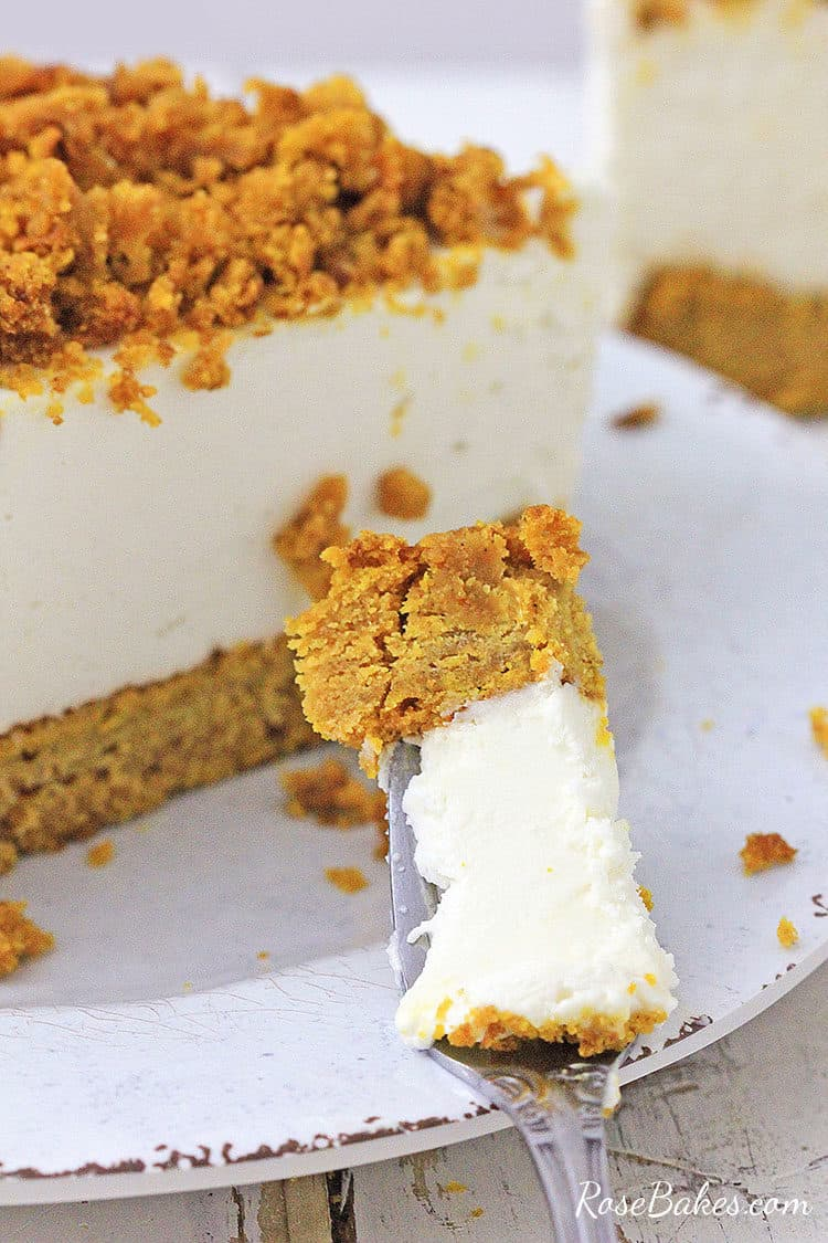 a bite of pumpkin bread bottom cheesecake on a fork leaning on a white plate