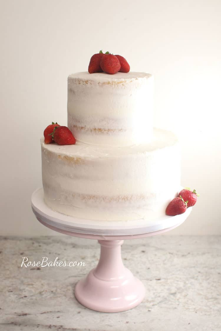 naked wedding cake with strawberries on a pink cake stand