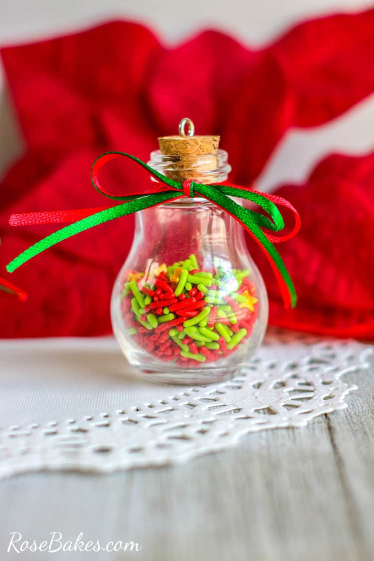 Glass Bulb Sprinkles Christmas ornament on a white table wtih ribbons
