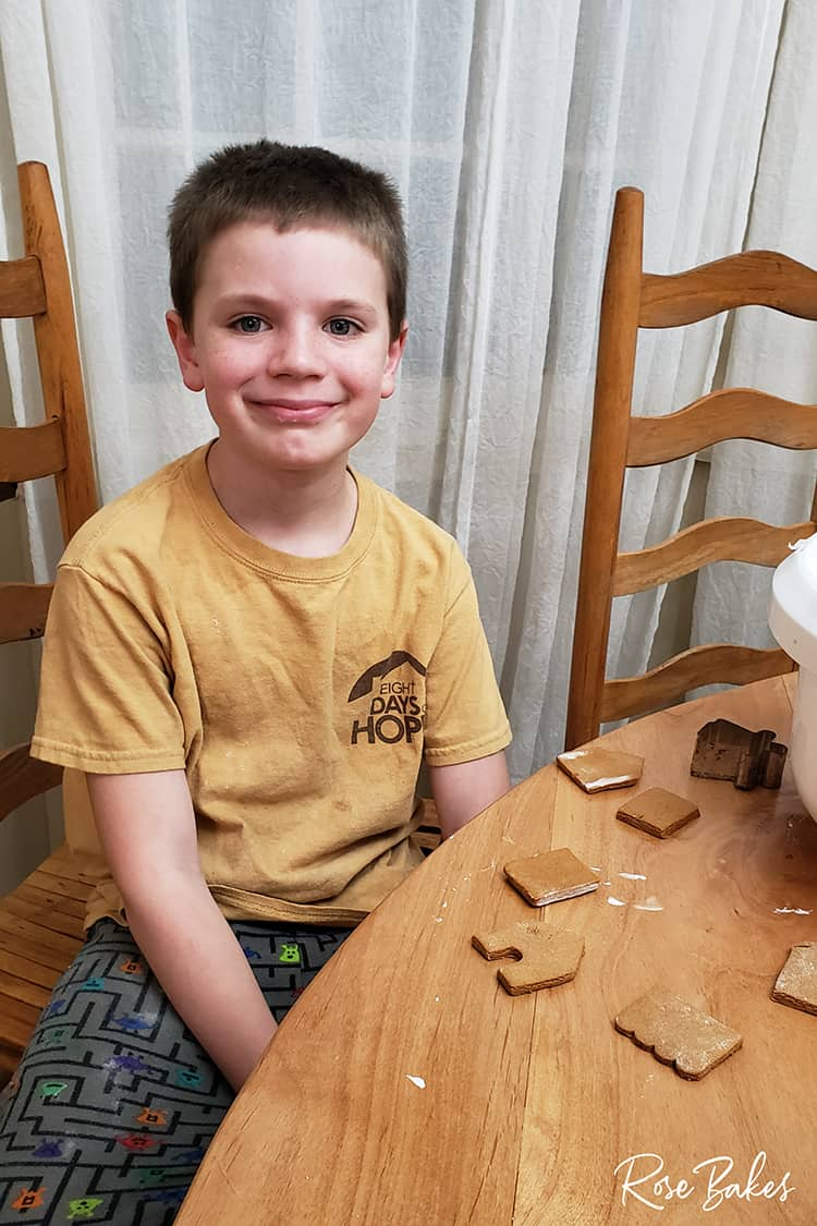 Kid building his gingerbread house