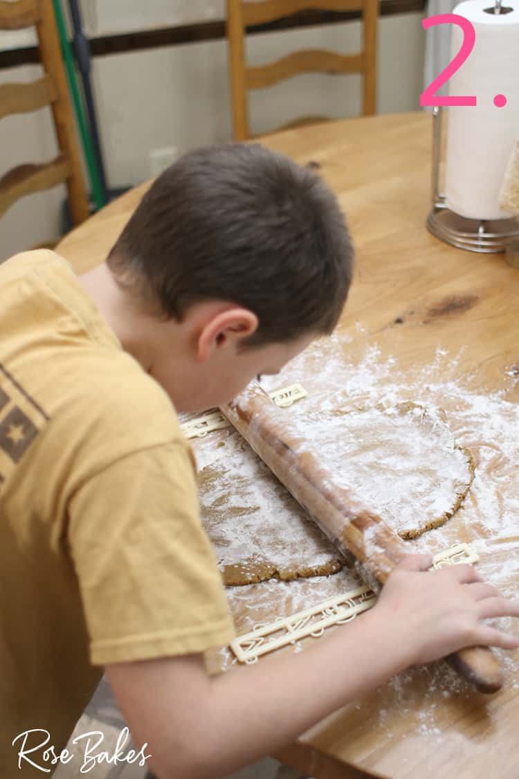 Kid rolling gingerbread dough on floured surface for How to Make Mini Gingerbread Houses with Kids post