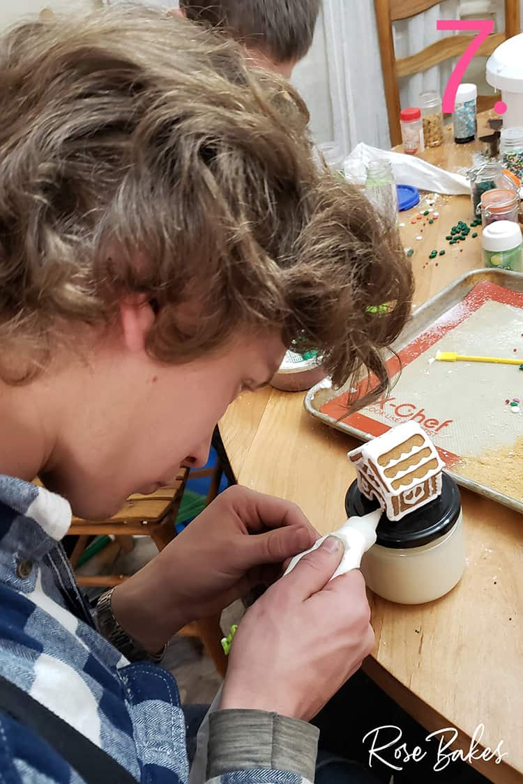 Young man decorating mini gingerbread house with icing