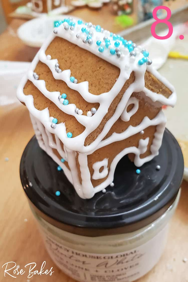 Mini gingerbread house drying on top of a lid