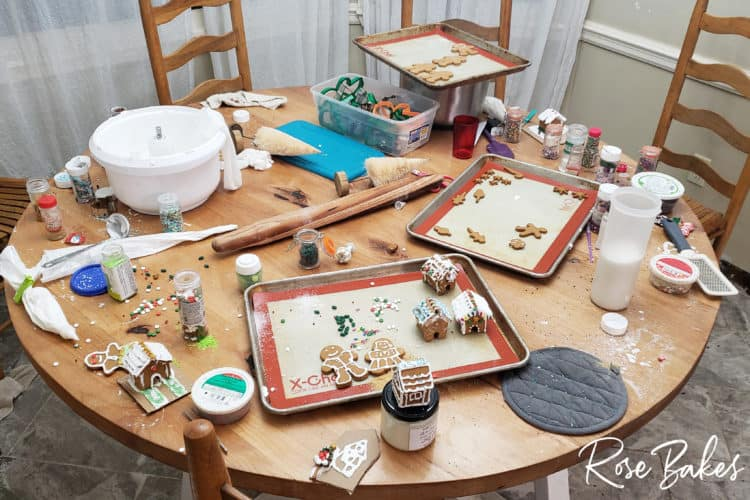 How to Make Mini Gingerbread Houses with Kids post - messy table with all the cookies, houses and supplies scattered