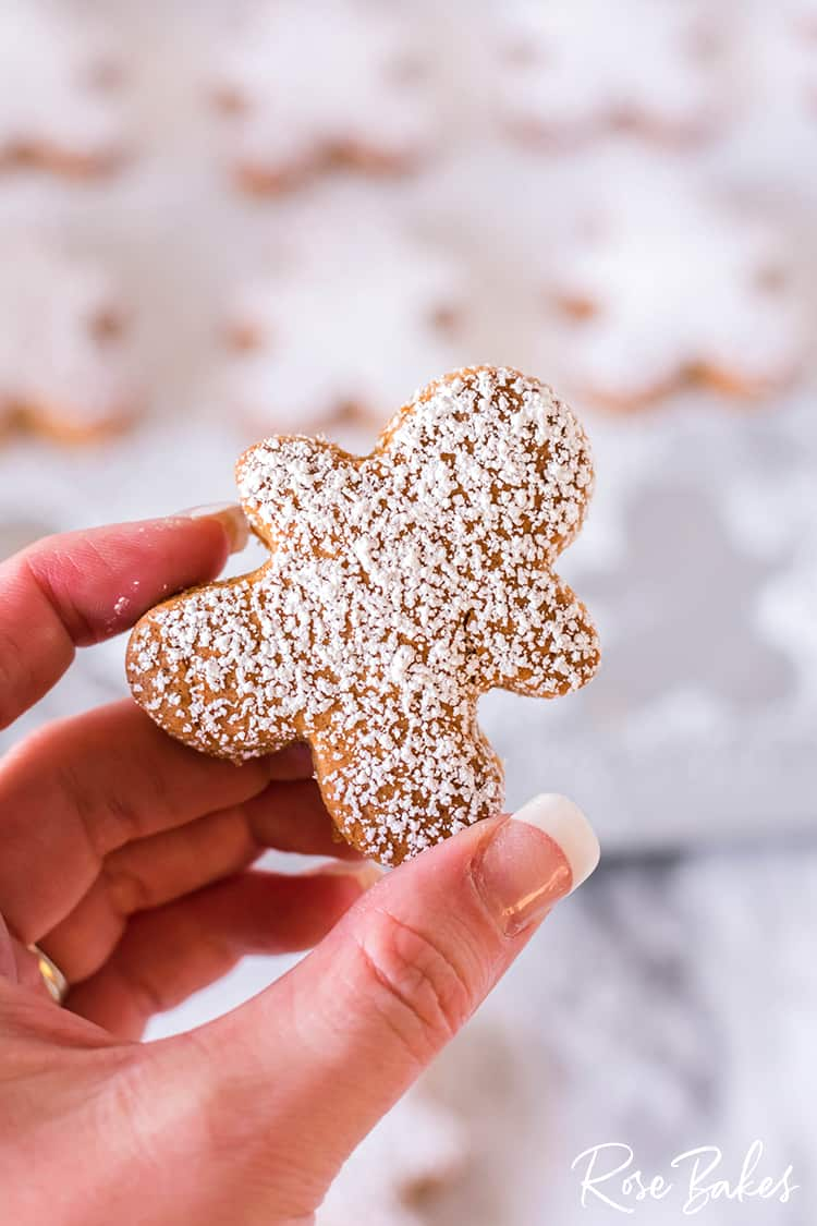 Mini Gingerbread Men Cookies with powdered sugar sprinkled on and being held