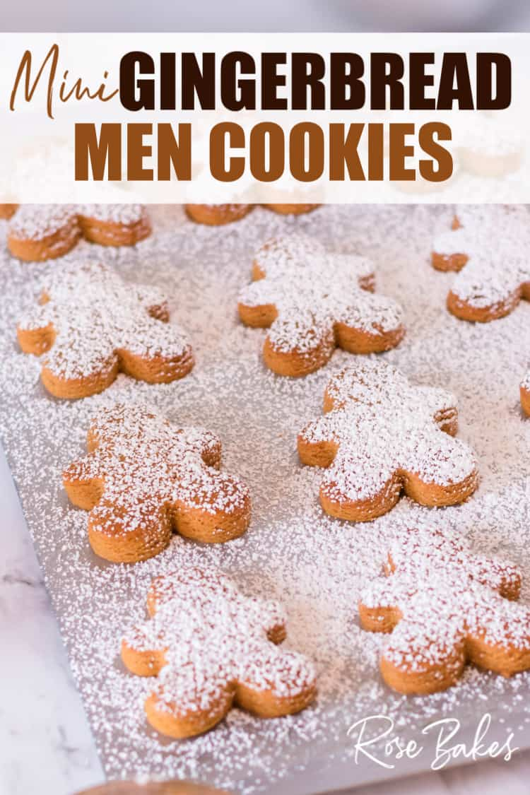Mini Gingerbread Men Cookies with powdered sugar sprinkled on a cookie sheet