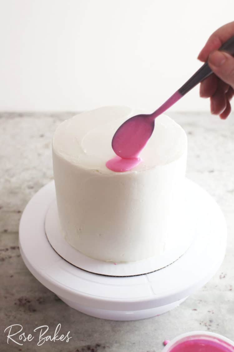 adding pink drip to canned frosting drip cake