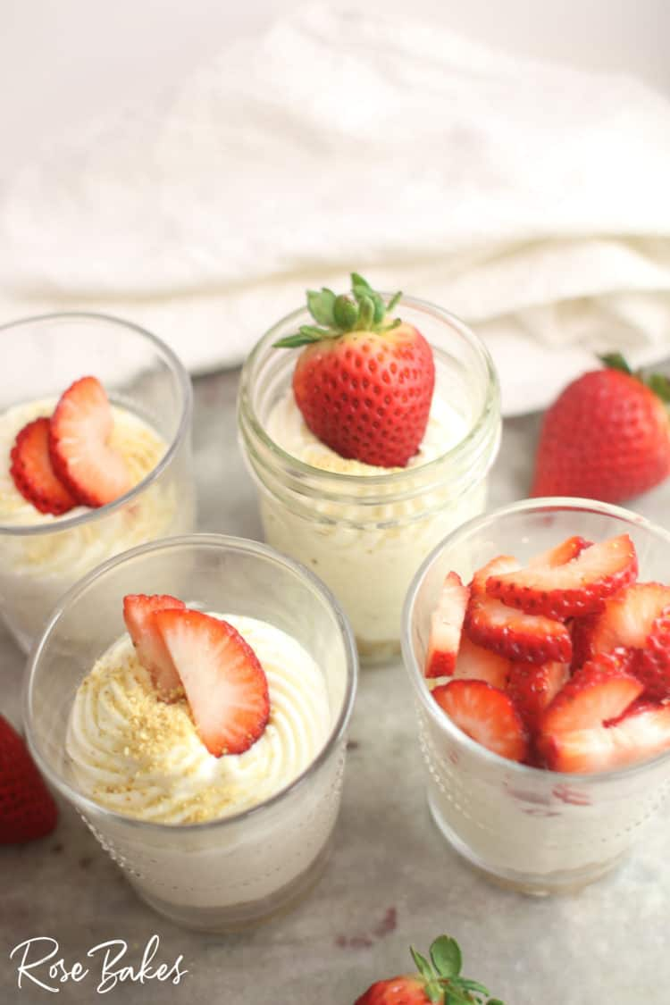 The creamiest No-Bake Cheesecake Cups Recipe in cups with strawberries on top