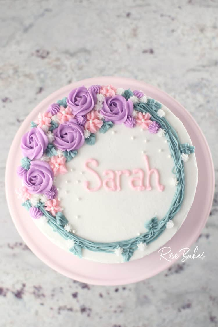 white cake with purple and pink buttercream wreath decorations