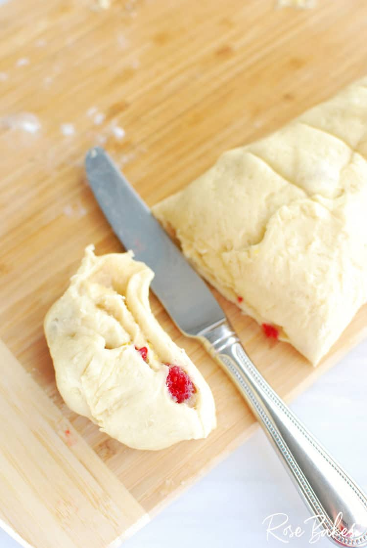 Raspberry Cinnamon Rolls dough rolled out on cutting board rolled up and ready for cutting