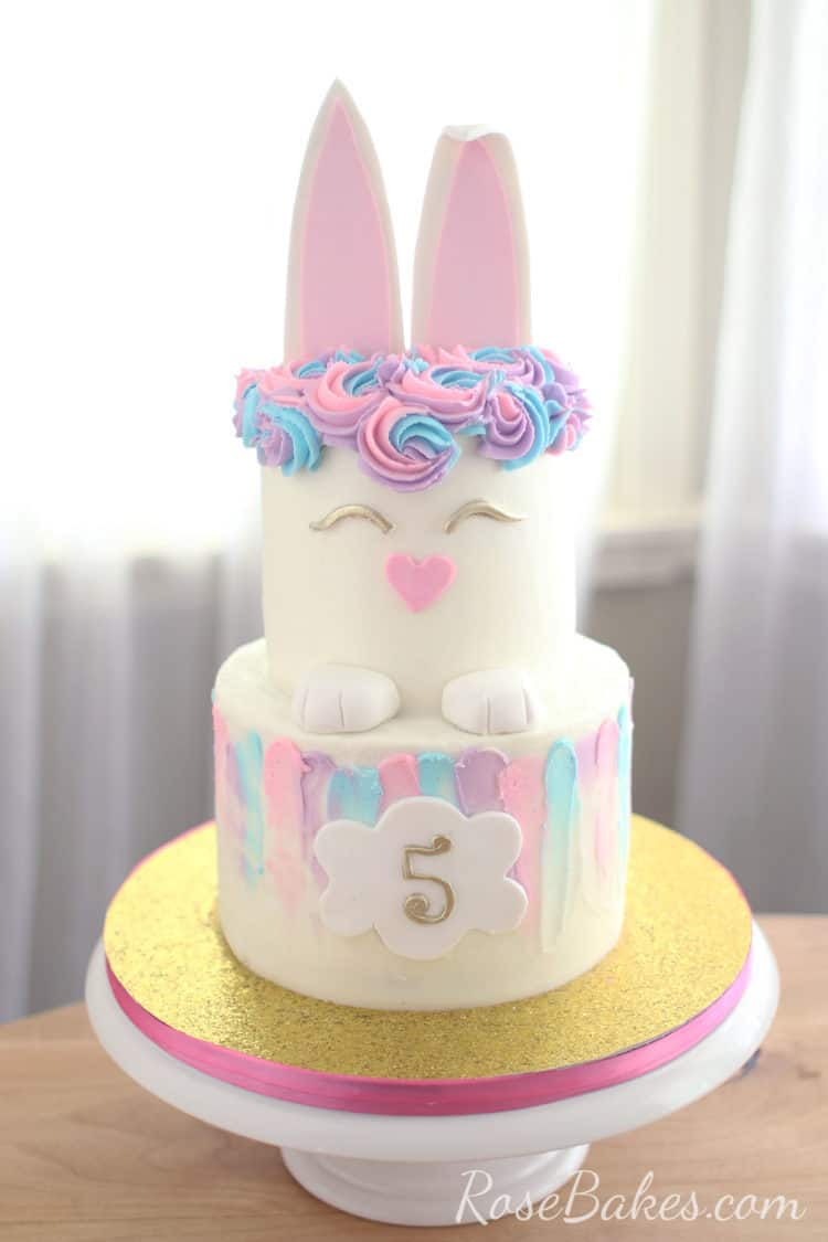 Buttercream 2 tiered cake with pastel pink, blue, and purple buttercream swipes around the top edge of the bottom tier. A fondant plaque with a gold 5 is on the front. The top tier is decorated like a bunny with bunny ears as the cake topper.