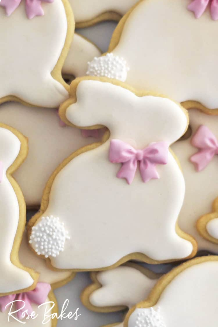 A close-up of a decorated Easter Bunny Cookie with a pink bow and nonpareil poofy tail