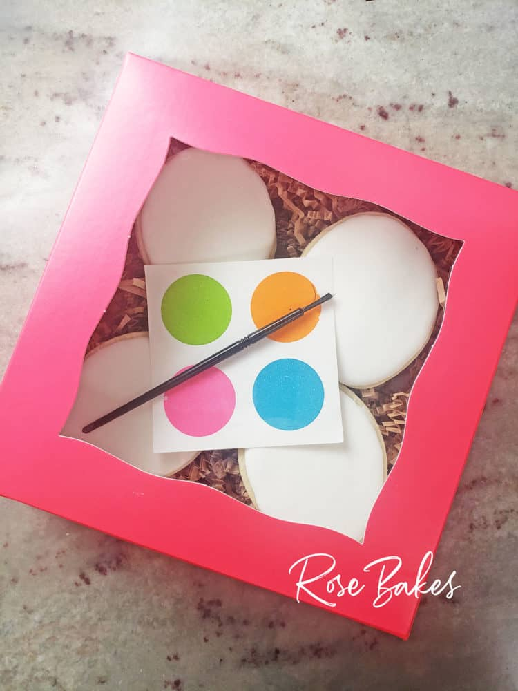 A pink box of blank cookies with a palette and paintbrush for Paint-Your-Own Cookie Sales..