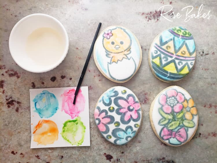 Stenciled cookies partially painted with a palette and paintbrush for PYO Cookie Party
