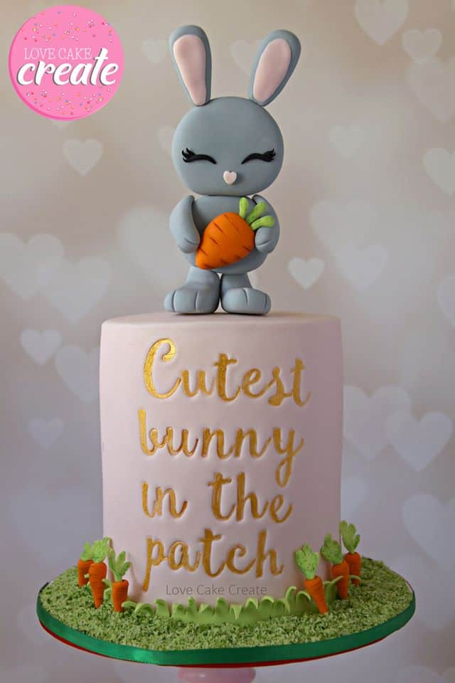 """Gray Bunny Topper holding a carrot and Carrot Patch on cake board. The cake reads """"Cutest bunny in the patch"""" on the front of the cake."""