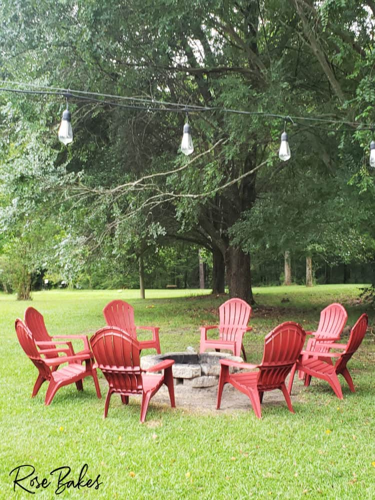 backyard with firepit and red adirondack chairs