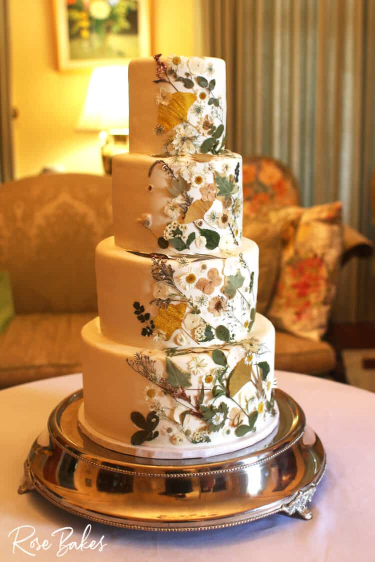side view of pressed flowers wedding cake on silver stand on table with white tablecloth