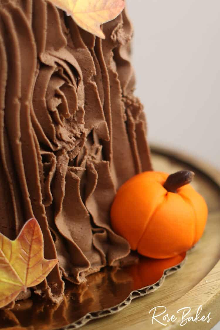 Easy Fall Tree Stump Cake closeup of chocolate buttercream, edible leaf and fondant pumpkin