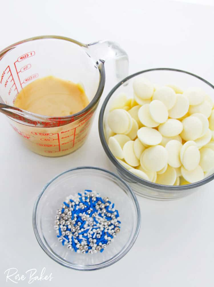 Sweetened condensed milk in a measuring cup, bowl of white chocolate wafer, and a small bowl of blue, white, and silver sprinkles