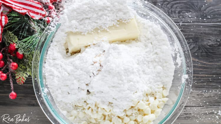 mixing bowl filled with cream cheese, cake mix, butter, white chocolate chips, and powdered sugar