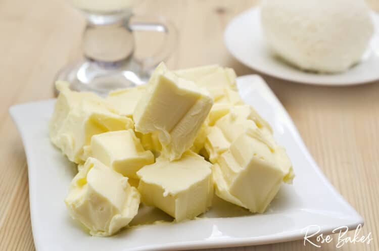 Cubed butter on a white plate coming to room temperature.