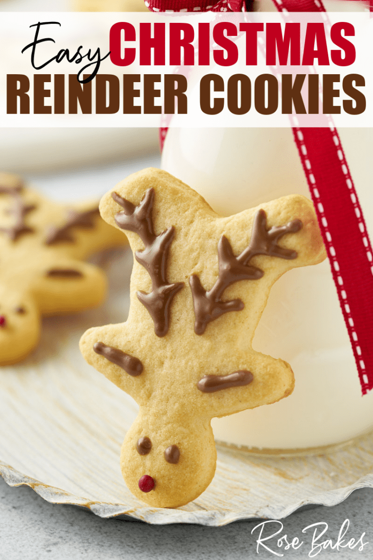 """A simply decorated Christmas reindeer cookie propped up against a glass of milk, with the text, """"Easy Christmas Reindeer Cookies"""""""