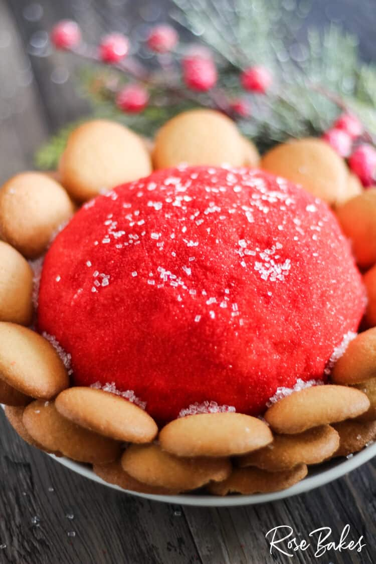 Cookie Dough Cheeseball rolled in red sparkling sugar with nilla wafers surrounding the ball. Christmas greenery in the background.