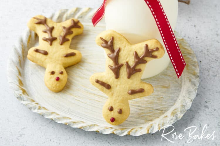 Two simply decorated Christmas reindeer cookies on a platter with one propped up against a glass of milk.