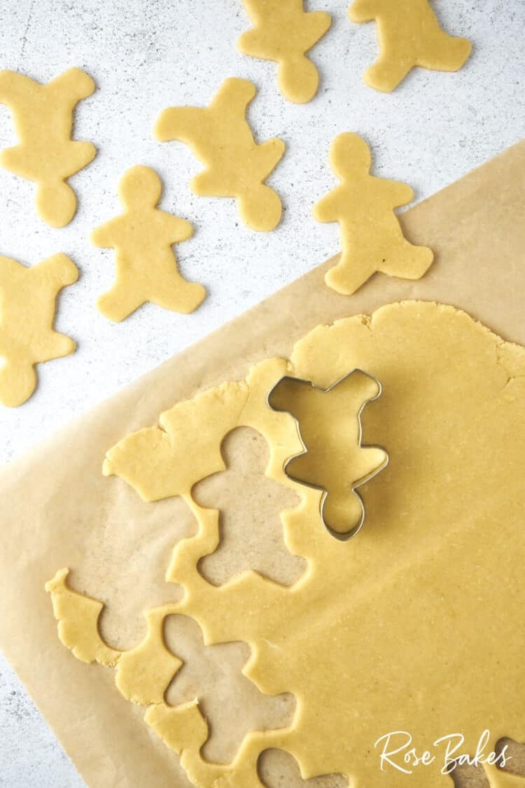 Sheet of cookie dough with shapes cut out with the gingerbread man cookie cutter.  It is turned upside down to make the reindeer shape.