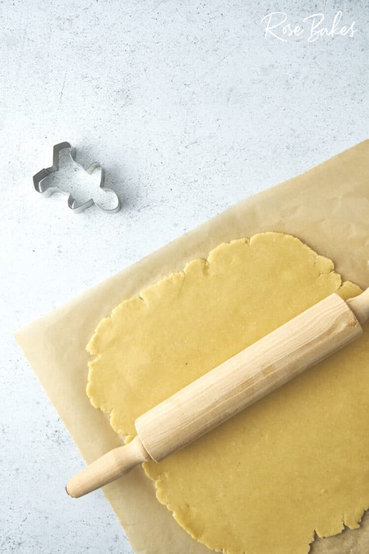 the cookie dough rolled out on a sheet of parchment.  A rolling pin sits on top of the dough and a gingerbread man cookie cutter is off to the side.