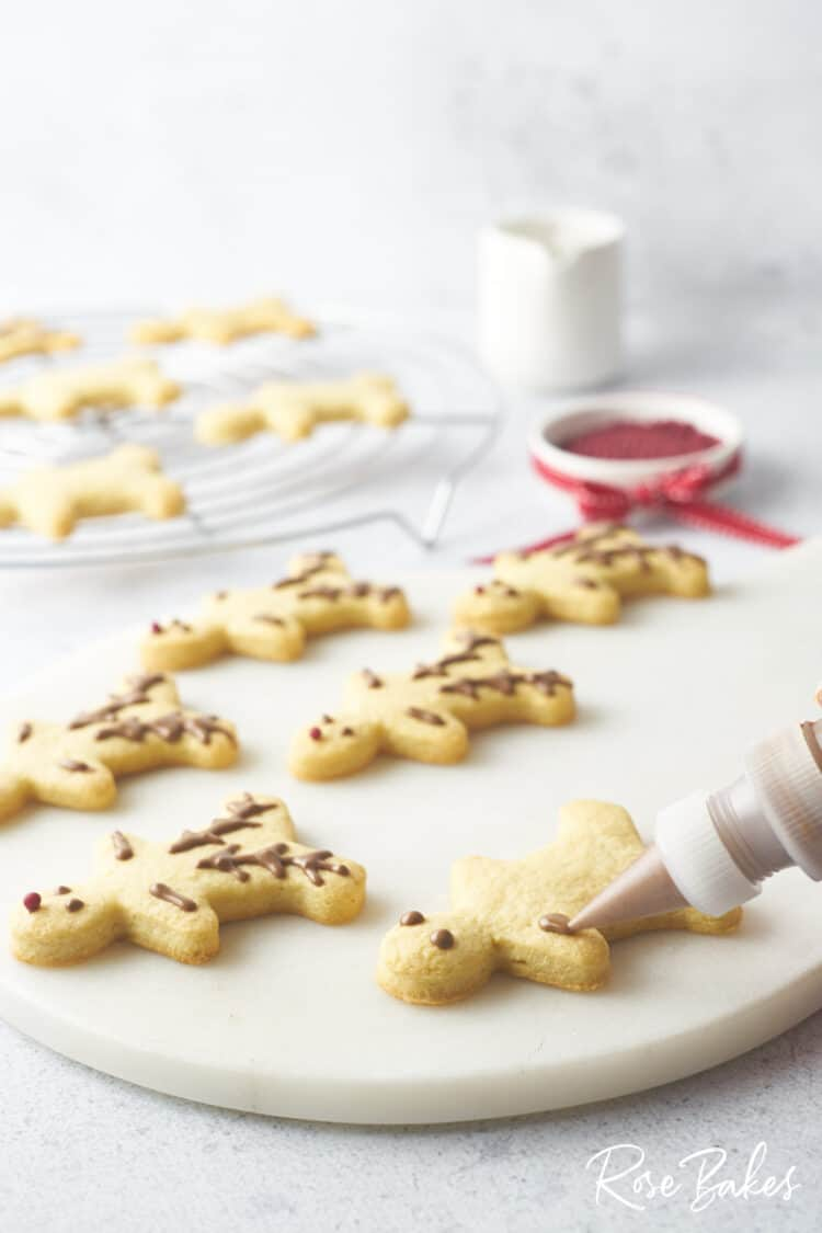 The cookies being decorated with melted chocolate.